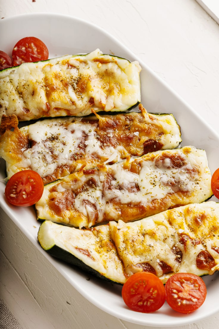 Melted cheese and tomato on top of zucchini.