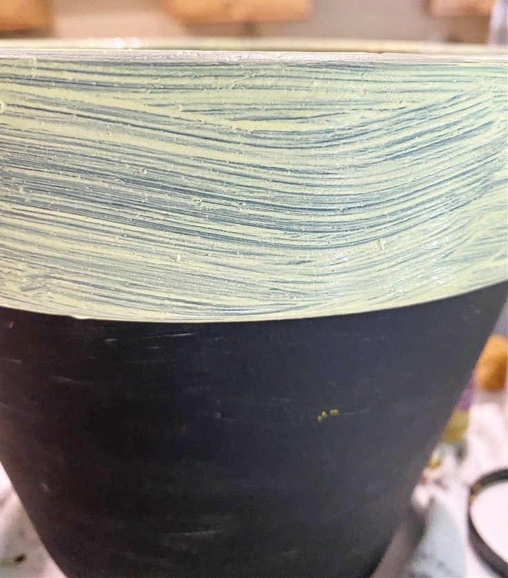 Painting yellow paint on rim of flower pot.