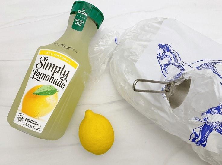 A bottle of Simply Lemonade, a whole lemon, and a bag of ice.