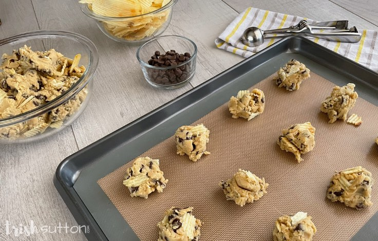 Drops of cookie dough on a pan with ingredients including potato chips and chocolate chips in the background.