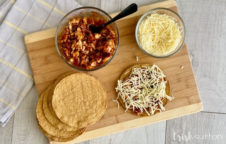 Ingredients for BBQ Chicken Tostadas on a wood cutting board.